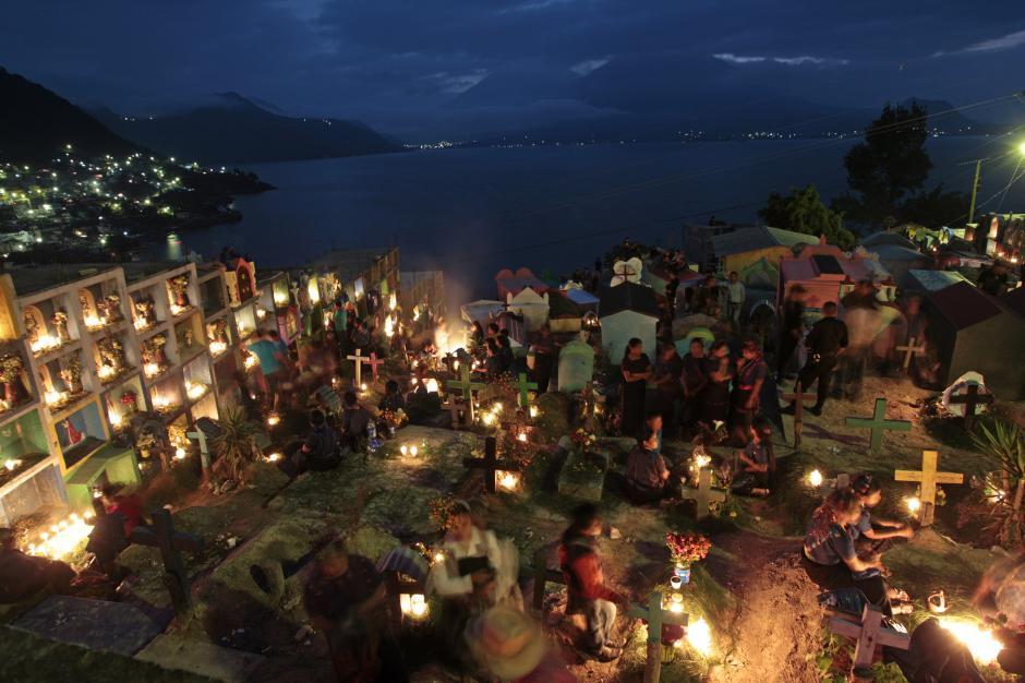 Cae la noche en San Antonio Palopó, y se iluminan las tumbas de los difuntos en el cementerio. Al fondo, el Lago de Atitlán. (Foto: Esteban Biba/ EFE)