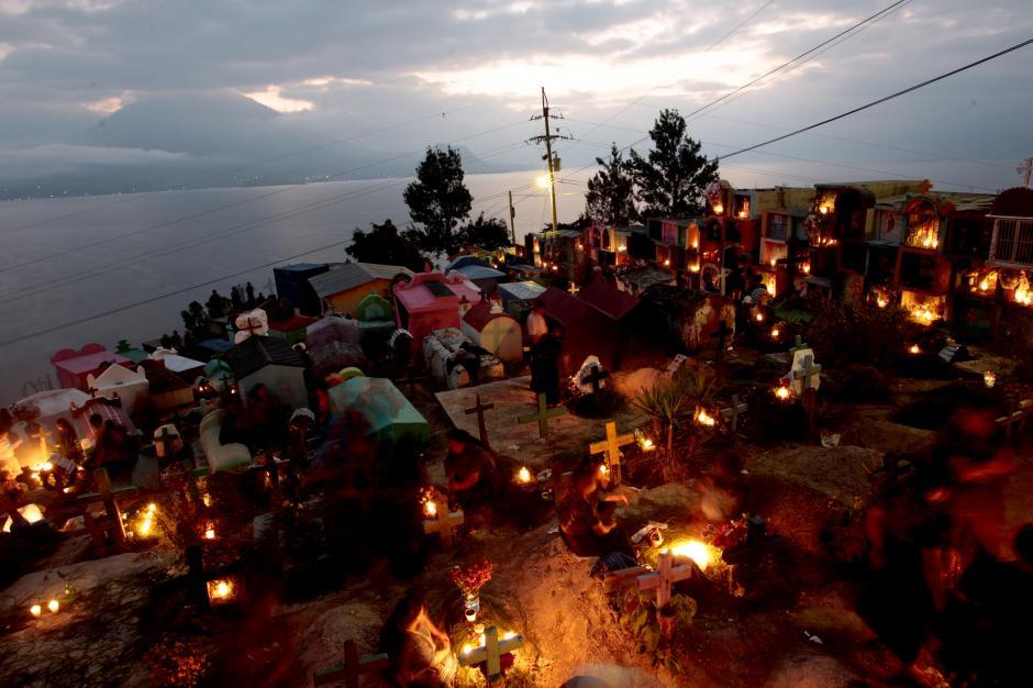 El sol se oculta y las tumbas de los difuntos se iluminan. Las familias acudieron al cementerio de San Antonio Palopó para honrar la memoria de sus muertos. (Foto: Esteban Biba/ EFE)
