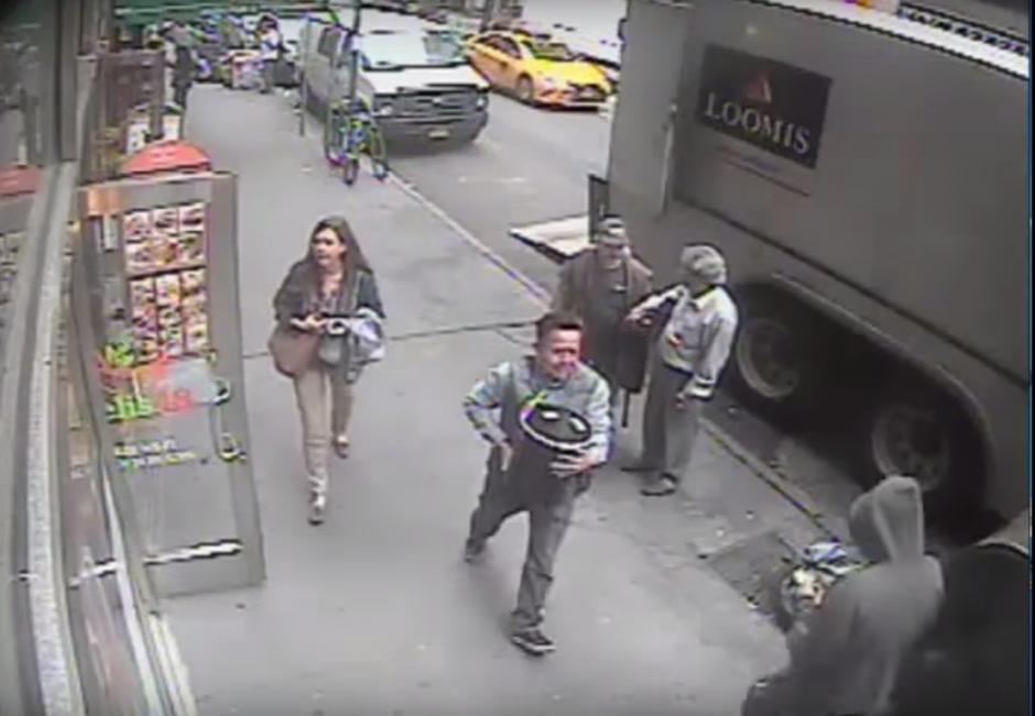 El hombre se aleja apresuradamente del camión a plena luz del día frente a otras personas. (Imagen: captura de YouTube)