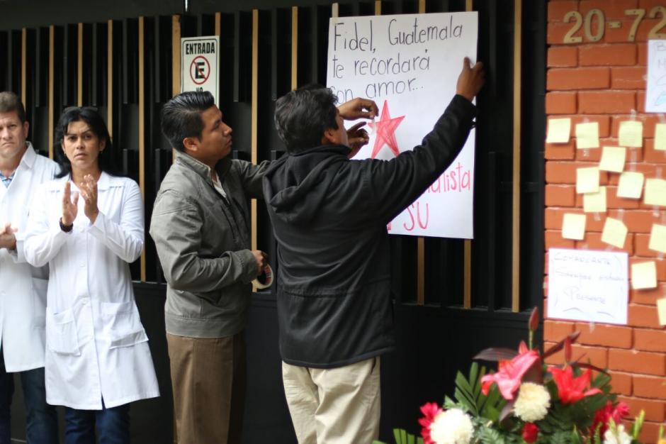 Dos hombres colocan un cartel en el que dice que Guatemala recordará con amor a Fidel Castro.  (Foto: Alejandro Balán/ Soy502)