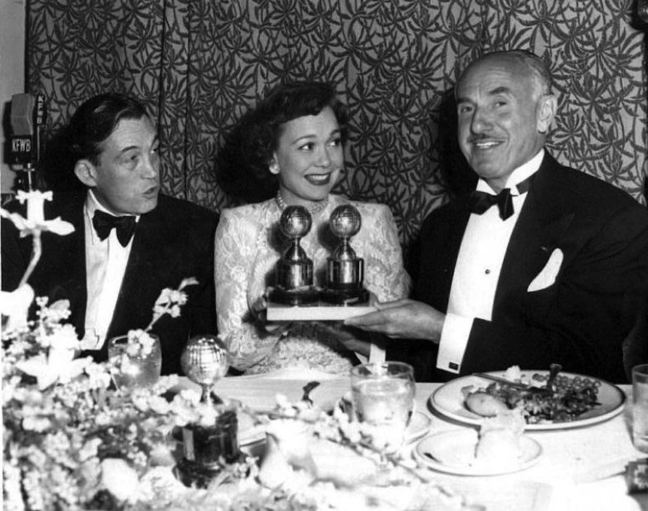 """En esta foto, los ganadores de la edición de 1949, disfrutan de la cena con sus galardones. John Hudson por la dirección de """"The treasure of the Sierra Madre"""", Jane Wyman mejor actriz por """"Johnny Belinda"""" junto a la cabeza de estudio Jack Warner. (Foto: Certaincinema)"""