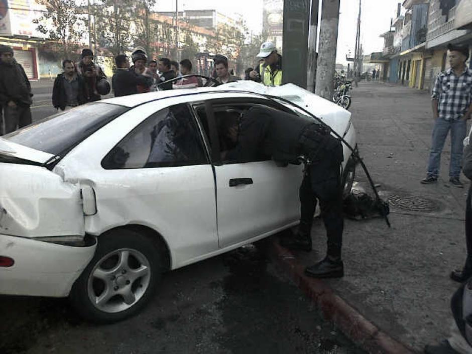Un agente de la PNC se acerca al vehículo colisionado para observar qué hay adentro. Posteriormente retira pertenencias del automóvil que sufrió el percance en la Avenida Petapa. (Foto: René Ruano/Nuestro Diario)