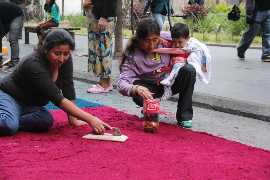 Familias completas participan en la elaboración de la alfombra. (Foto: Antonio Ordóñez/Soy502)