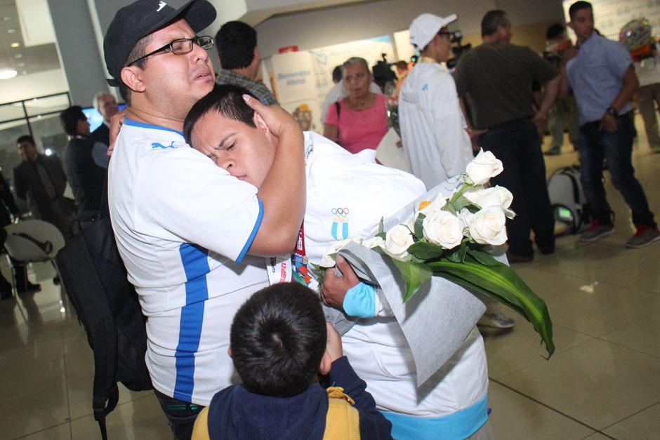 Leonardo Quevedo, uno de los medallistas, recibe un abrazo tras arribar a Guatemala. (Foto: José Dávila/Soy502)