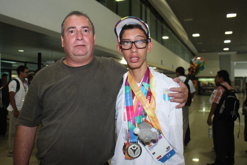 Eduardo Guerra, medalla de plata en 1,500 metros en aguas abiertas, posa junto a un familiar. (Foto: José Dávila/Soy502)