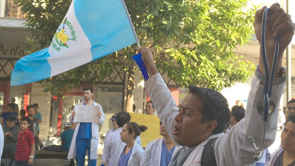 Un médico residente levanta con una mano la bandera y con la otra, un estetoscopio. (Foto: Luis Barrios/Soy502)