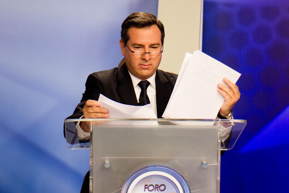 Luis Fernando Pérez revisa hojas que le sirvieron como apoyo para contestar la preguntas del foro. (Foto: Alejandro Balan/Soy502)