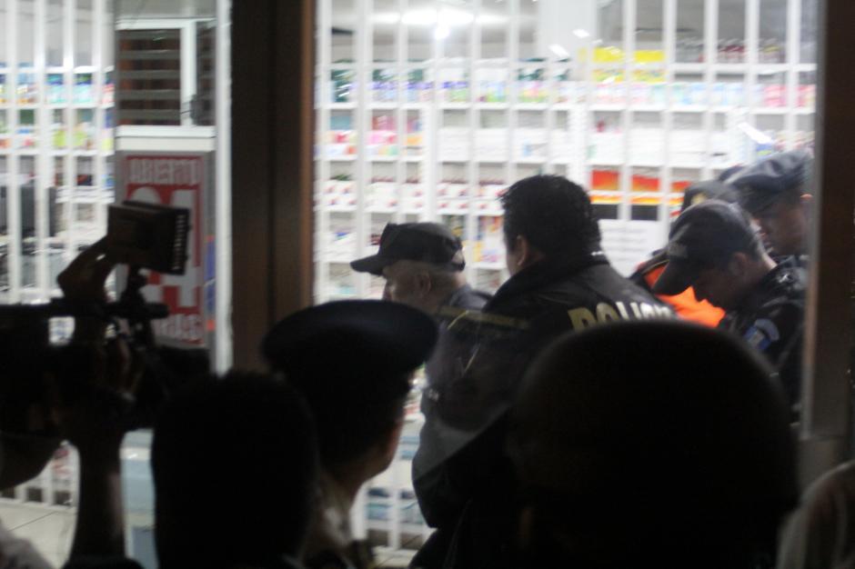 El guardia de seguridad Mynor Guevara es retirado por la Policía de la farmacia Galeno donde abatió a sangre fría a la funcionaria municipal Patricia Samayoa. (Foto Alexis Batres/Soy502).