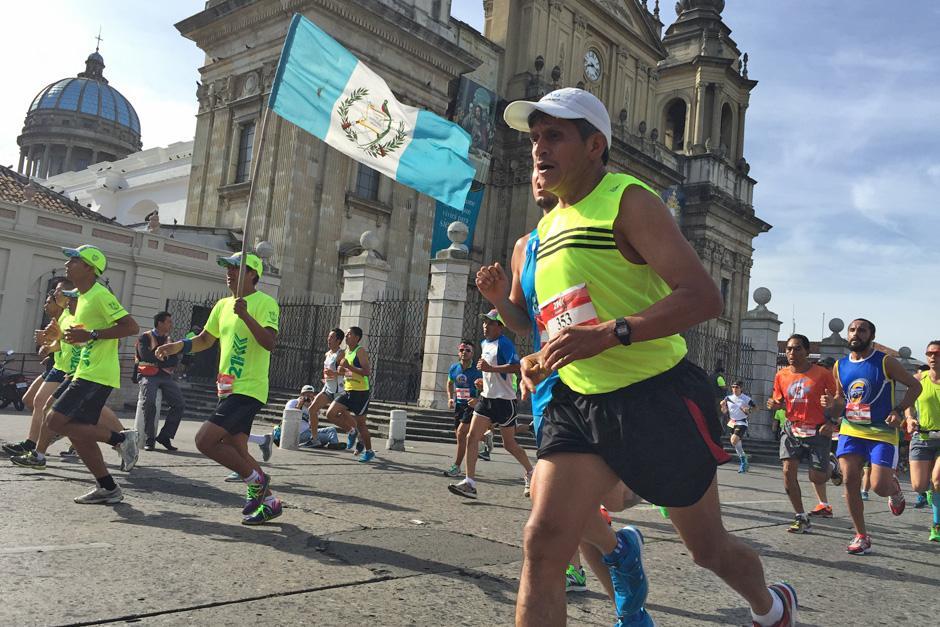 Un competidor alza una bandera de Guatemala mientras corre.