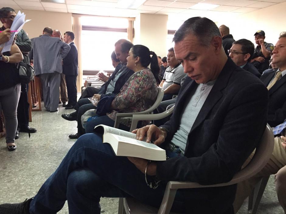 Juan de Dios Rodríguez, expresidente de la Junta Directiva del IGSS, lee la Biblia mientras espera el inicio del juicio en su contra. (Foto: Evelyn de León/Soy502)