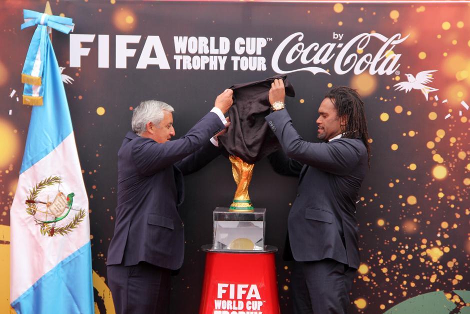 El presidente, Otto Pérez, junto al ex futbolista y campeón de Mundo, el francés Christian Karembou, develan el trofeo de la Copa del Mundo, en su llegada a Guatemala en el Aeropuerto La Aurora. (Foto: Luis Barrios/Soy502)