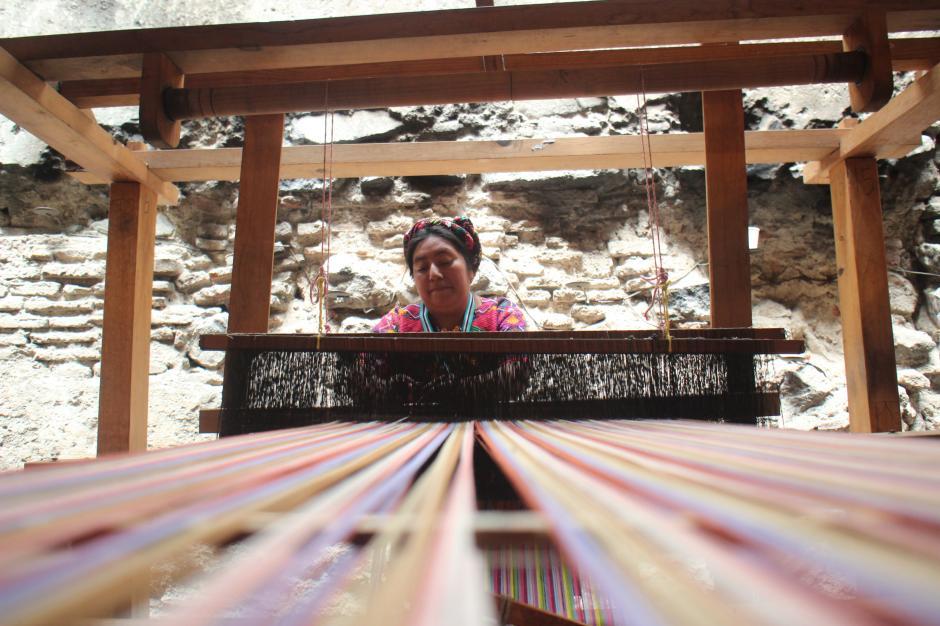 Mujer tejiendo en un telar de pie durante la exhibición.(Foto: Alejandro Balán/Soy502)