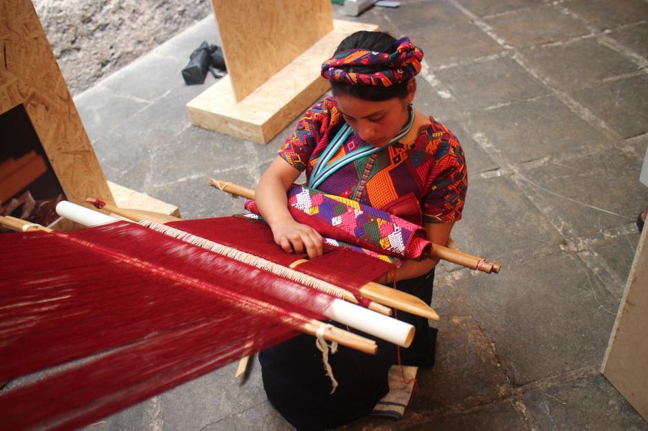 Una joven tejía en un telar durante la exhibición. (Foto: Alejandro Balán/Soy502)