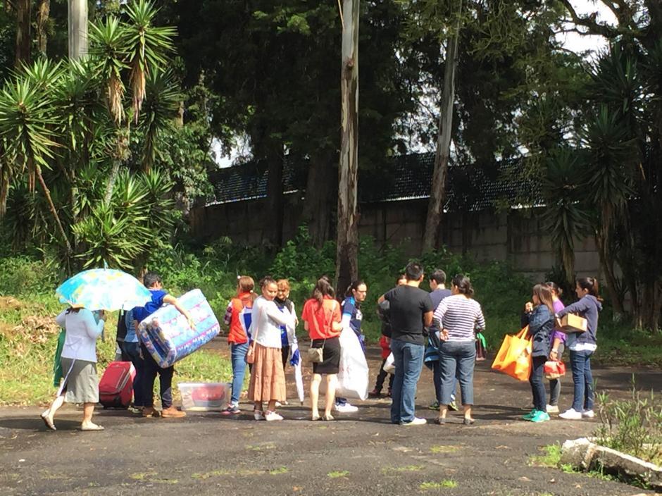 Familiares de los privados de libertad recluidos en Mariscal Zavala llevan enseres; se observa que un joven carga un colchón. (Foto: Evelyn de León/Soy502)