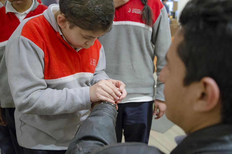 """Los niños regalaron una """"Pulsera Mágica"""" a los asistentes que """"al momento de colocártela una corriente eléctrica va directamente a tu corazón"""", explicaron. (Foto: Magui Medina/Soy52)"""
