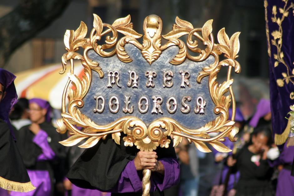 Un letrero dorado anuncia la llegada de la Virgen Dorolorsa en la procesión de La Parroquia Vieja del Lunes Santo. (Foto: Raúl Illescas).