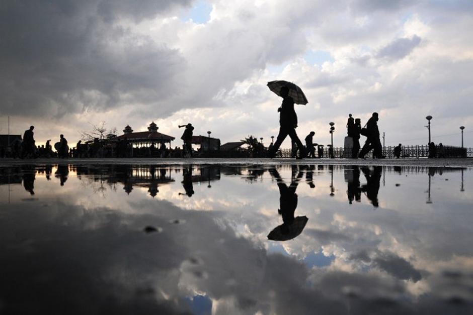Pobladores de la India caminan por una calle después de una tormenta de granizo en la colina de la ciudad norteña de Shimla, sucedida este 22 de marzo de 2014. El clima frío y lluvias ha seguido afectando a partes del norte de la India. (Foto: AFP)