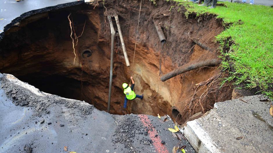 Un empleado municipal desciende por el agujero. En esta toma, se observa que al menos tendría unos diez metros de profundidad. (Foto: Jesús Alfonso/Soy502)