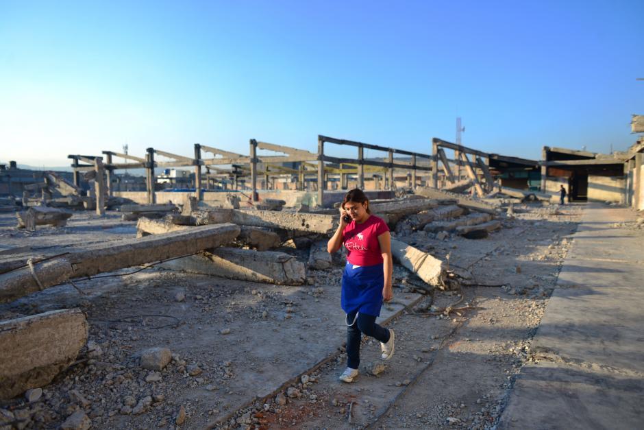 Una jovencita cruza el área donde fue el incendio, la que aún se encuentra cubierta por escombros y columnas rotas. (Foto: Jesús Alfonso/Soy502)