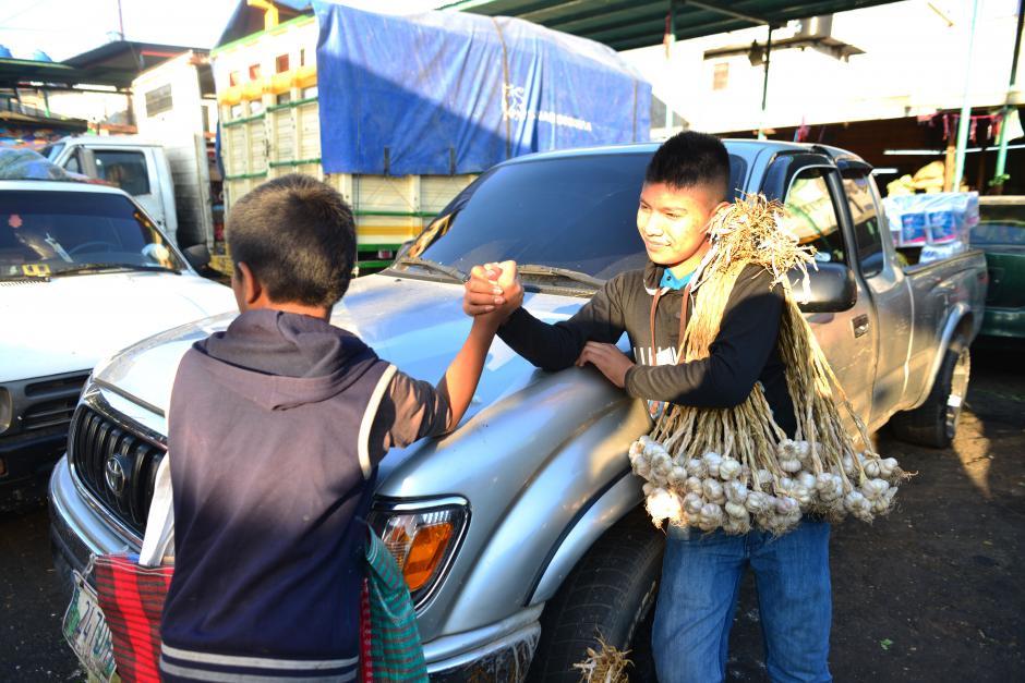 Dos niños se toman un tiempo para jugar y luego continuar con sus labores en los alrededores del mercado. (Foto: Jesús Alfonso/Soy502)