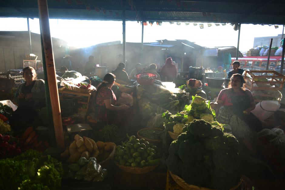 Los rayos del sol alumbran tímidamente a las vendedoras que, a las siete de la mañana, ya tenían más de cinco horas de estar en el lugar. (Foto: Jesús Alfonso/Soy502)