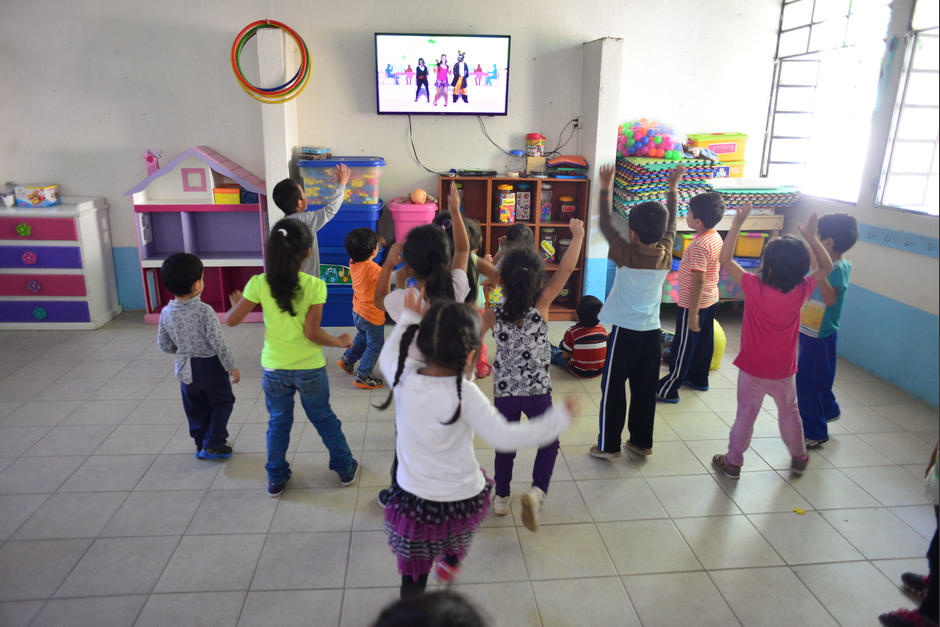 Los niños más pequeños bailan y cantan frente a un televisor mientras esperan para recibir sus clases. (Foto: Jesús Alfonso/Soy502)