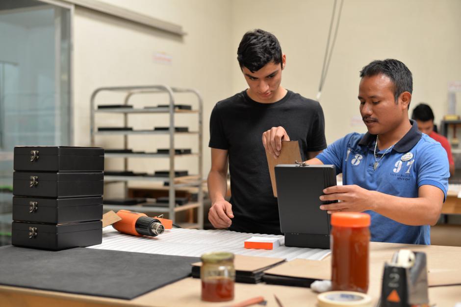 Diego Guzmán ayuda a pintar y pegar unas cajas que fabrican para un pedido de una empresa. (Foto: Wilder López/Soy502)