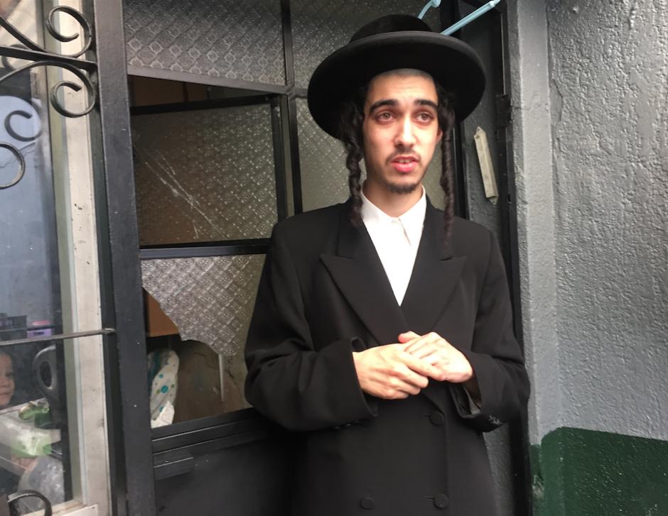 Un miembro de la comunidad judía Lev Tahor muestra el vidrio de la ventana que quebraron los agentes de Policía y se quejó por lo que consideró exceso de fuerza. (Foto: Evelyn de León/Soy502)
