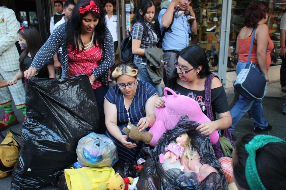 Las chicas Pin Up guatemaltecas organizan los juguetes que reunieron durante la tarde del sábado en un pequeño espacio en la banqueta. (Foto: José Dávila/Soy502)