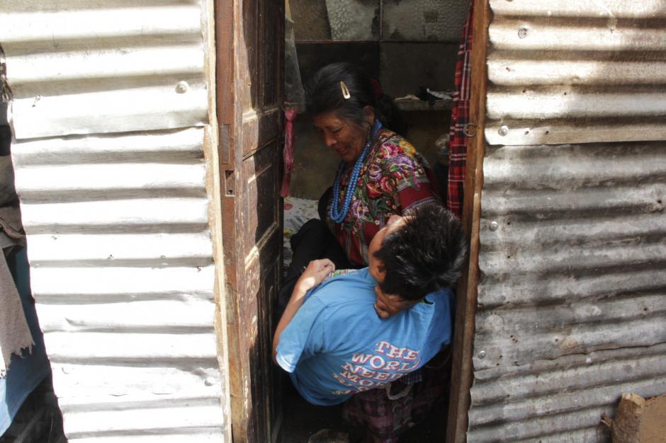 Aún con muchas fuerzas, la sexagenaria dama traslada a su hijo hacia su cama. (Foto: Fredy Hernández/Soy502)