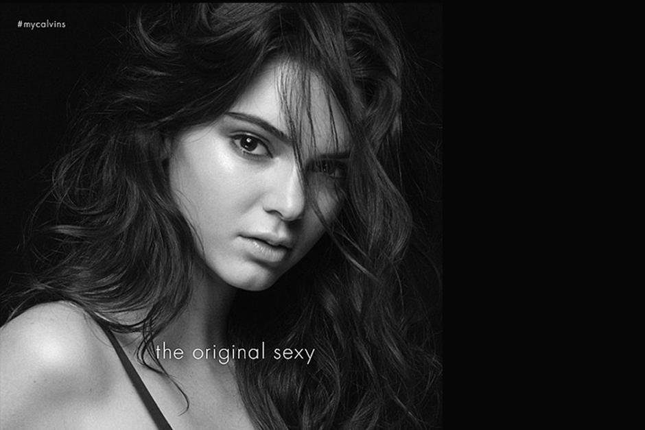 La modelo tiene un conjunto de ropa interior negro y mira de manera sugerente a la cámara.