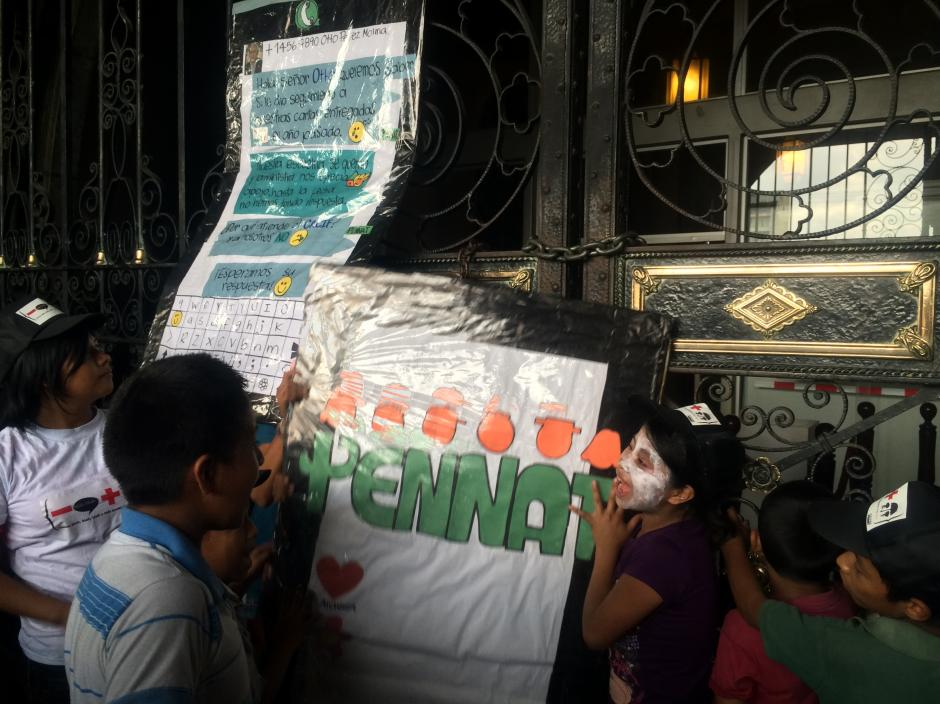 Niños de Pennat dejan su mensaje para Otto Pérez Molina colgado en la puerta del Palacio Nacional, ya que durante tres años los mandatarios no han querido recibirlos. (Foto: Luis Barrios/Soy502)