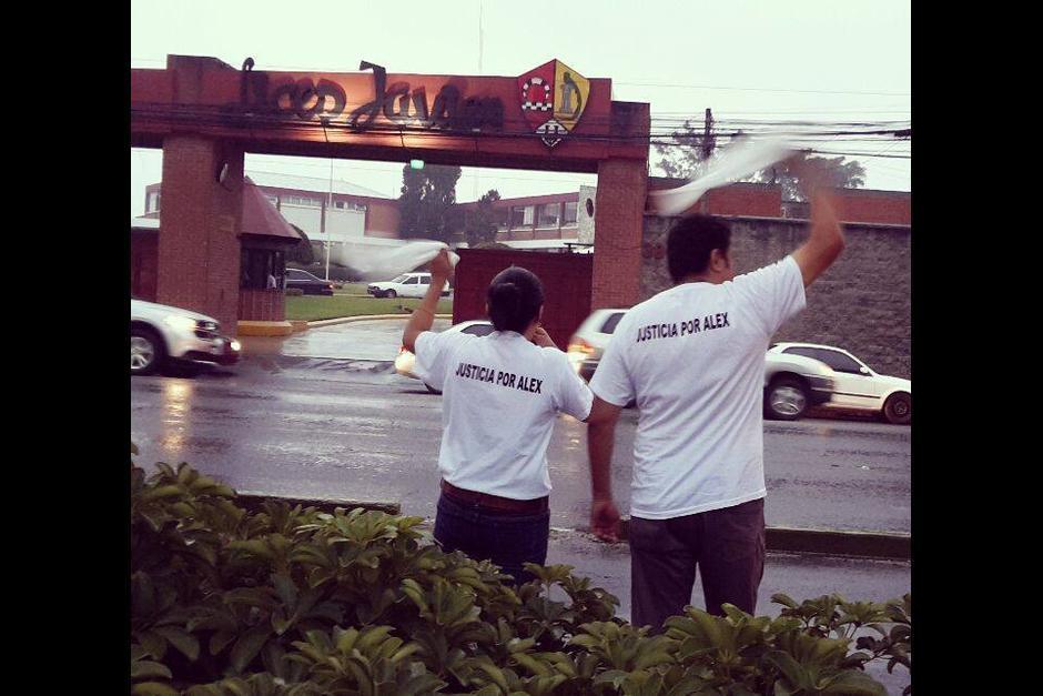 Los padres de Alex frente al Liceo Javier donde colocaron listones blancos. (Foto: Facebook)