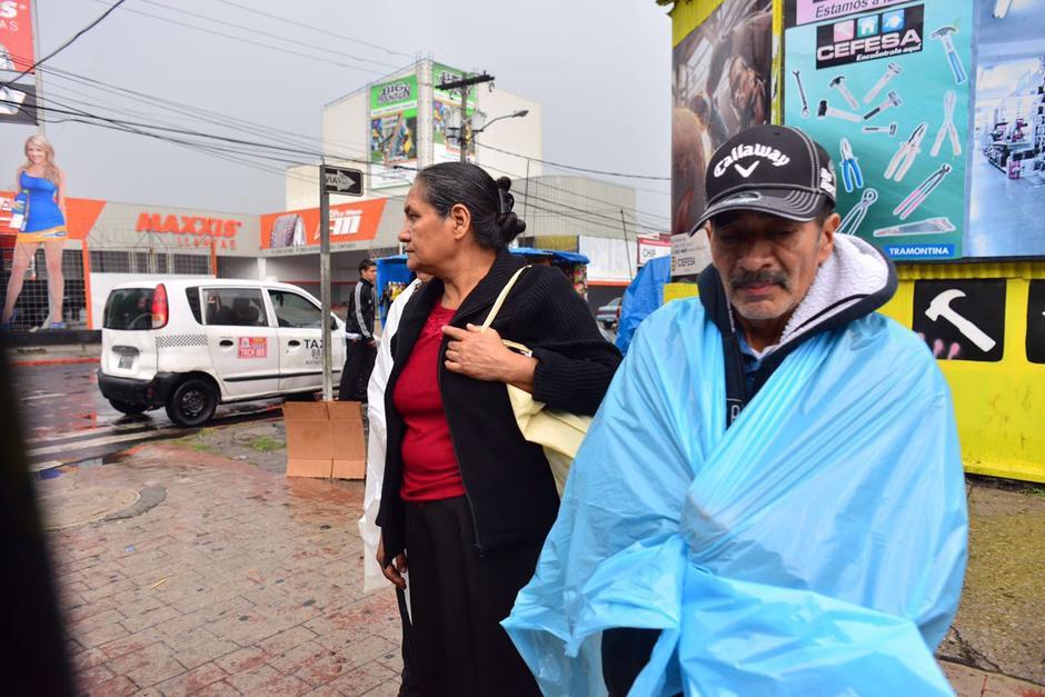 Los guatemaltecos buscan la forma de protegerse de la lluvia. (Foto: Jesús Alfonso/Soy502)