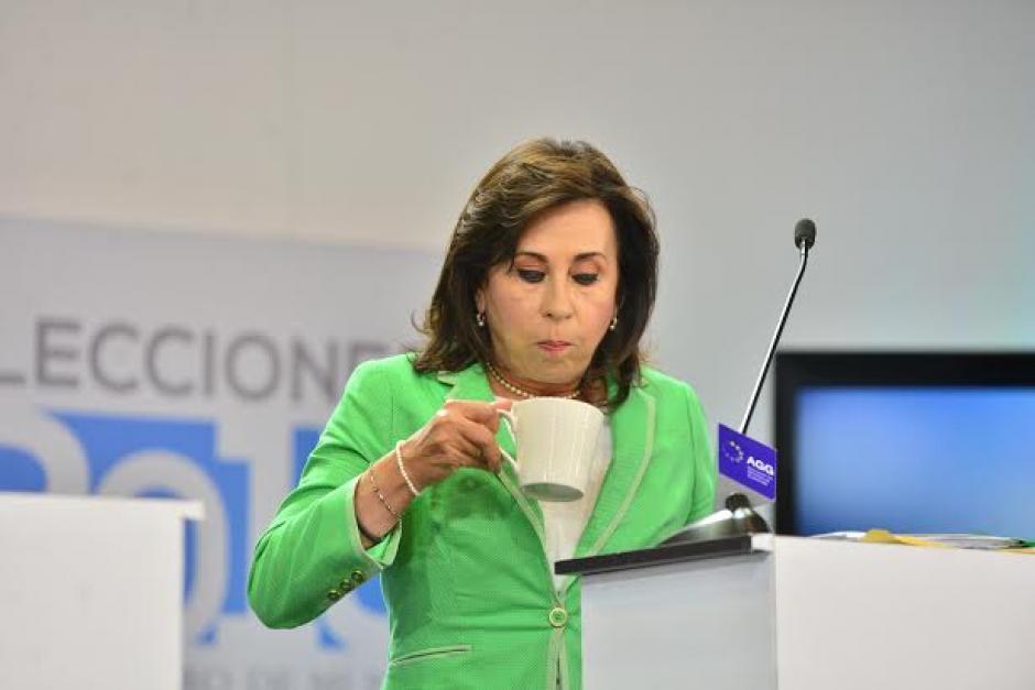 Sandra Torres toma una bebida que su equipo de trabajo lleva en un termo, mientras mandan a comerciales en el debate. (Foto: Wilder López/Soy502)