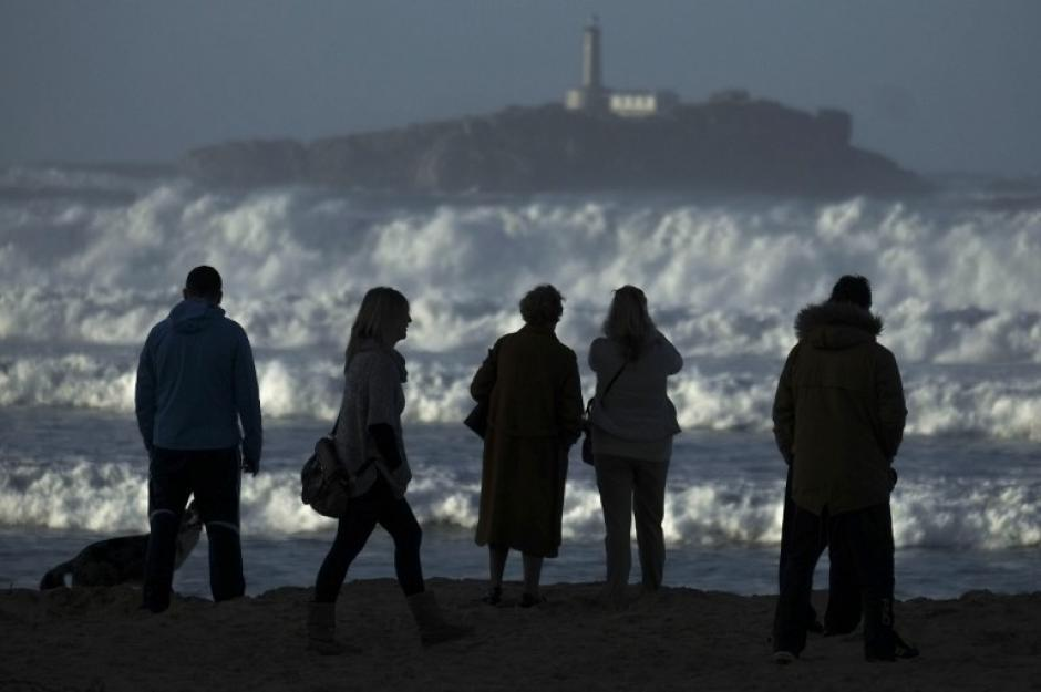 La gente mira a las olas en la playa de Somo en Ribamontan del Mar, cerca de Santander, España el 6 de febrero de 2014. Furiosas olas golpeaban paseos marítimos y barcos de pesca frente al norte de España, donde las autoridades emitieron alertas de mareas de tormenta y vientos fuertes para el miércoles, con el pronóstico de la nieve en algunos lugares. AFP PHOTO / PEDRO ARMESTRE