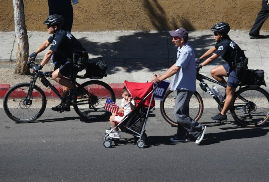 Inmigrantes hispanos recorrieron este sábado las calles de Los Angeles, California, en demanda de la inmediata aprobación de la Reforma Migratoria que garantizaría mejores derechos para ellos y sus familias. En la imagen, uno de los migrantes empuja el carruaje de su bebé, mientras es custodiado por policías que siguieron el recorrido en bicicletas.