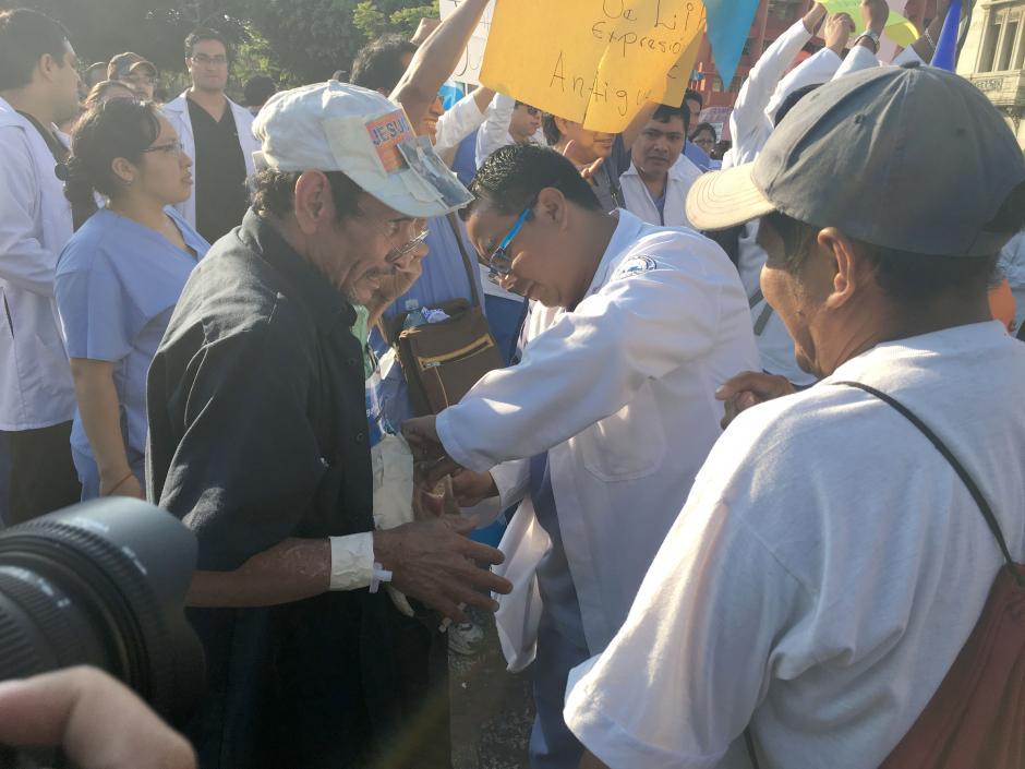 Un médico residente que participaba en la marcha para pedir mejores condiciones laborales, no dudó en atender a un adulto mayor que necesitaba apoyo en el Parque Central. (Foto: Luis Barrios/Soy502)