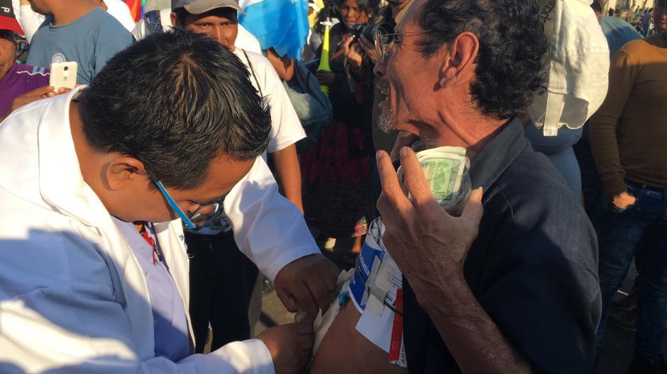 El médico residente que atendió a un paciente en el Parque Central, recibió en pago una sonrisa del enfermo que necesitaba ayuda para colocarse una bolsa de colostomía. (Foto: Luis Barrios/Soy502)