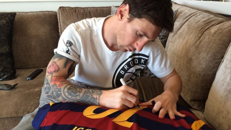 Lionel Messi escribe un mensaje especial en la camiseta que le envió como regalo a su amigo Ronaldinho para esta navidad. (Foto: FC Barcelona)