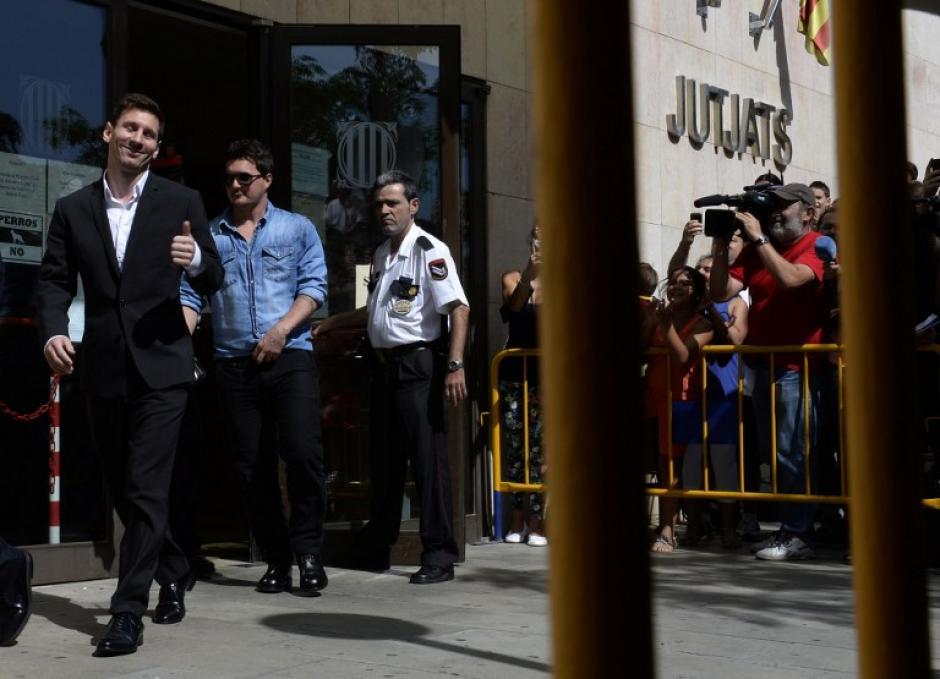 Lionel Messi del Barcelona de fútbol le da el visto bueno al salir de la courthouse en la ciudad costera de Gavà, cerca de Barcelona el 27 de septiembre de 2013, transcurrida la audiencia por cargos de evasión de impuestos. Messi y su padre son acusados de tratar de engañar al fisco español por una suma de € 4.000.000 ($ 5.000.000, £ 3,4 millones) por la cesión de derechos de imagen del jugador para las empresas con sede en paraísos fiscales como Belice y Uruguay. (Foto: AFP/ LLUIS GENE)