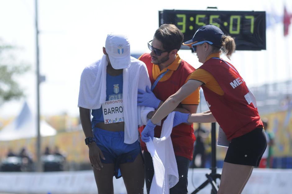 Barrondo es asistido por voluntarios en Toronto tras cruzar la meta de la prueba de 50 kilómetros de marcha