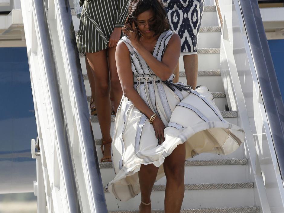 Michelle Obama tuvo que luchar contra el viento para que no se le levantara el vestido. (Foto: Elespañol)