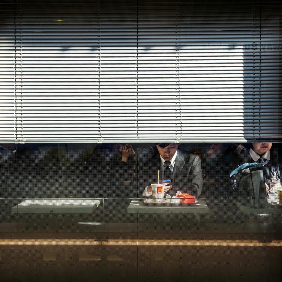 Un hombre mira su celular luego de comer en un restaurante de comida rápida, en Japón son populares las mesas para una sola persona. (Foto: Turi Calafato/National Geographic)