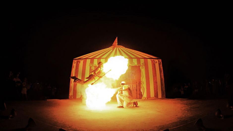 Una pareja de artistas realiza un performance lanzando bolas de fuego por la boca. (Foto: Ari Fararooy)