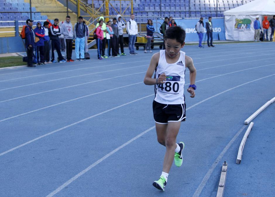 Luis Luciano Tzunún, de Quiché, fue el ganador la categoría 3000 metros varoniles, Sub 14. Al fondo de su competencia, los seleccionados de marcha observan la carrera. (Foto: Federación de Atletismo)