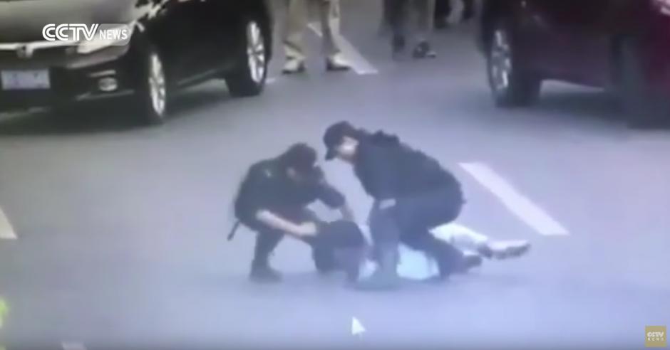 Cuando el sujeto ya se encuentra en el suelo desarmado, sus compañeros la ayudan. (Captura de pantalla: CCTV News /YouTube)
