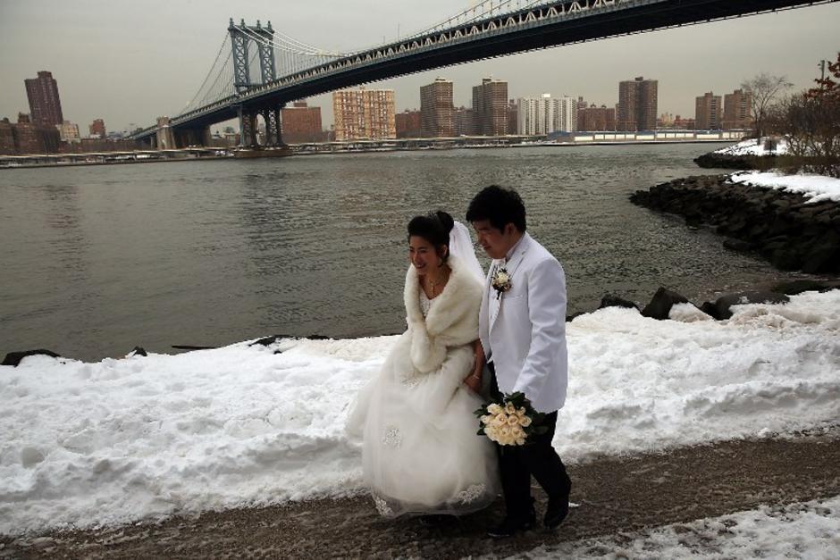 Una pareja de recien casados fueron captados mientras caminaban en los alrededores del puente de Manhattan. La tormenta dejó 26.8 pulgadas en Manhattan, el segundo mayor registrado desde 1869. (Foto: AFP/ Spencer Platt)