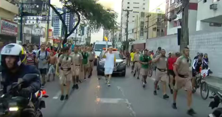 Nikita, un ex entrenador de natación de la selección brasileña llevaba la antorcha Olímpica. (Captura de pantalla: Tem Muito/YouTube)