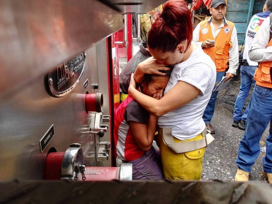 La hermana de las fallecidas fue consolada por la bombero Alejandra Giraldo. (Foto: Gustavo E. Méndez/Soy502)